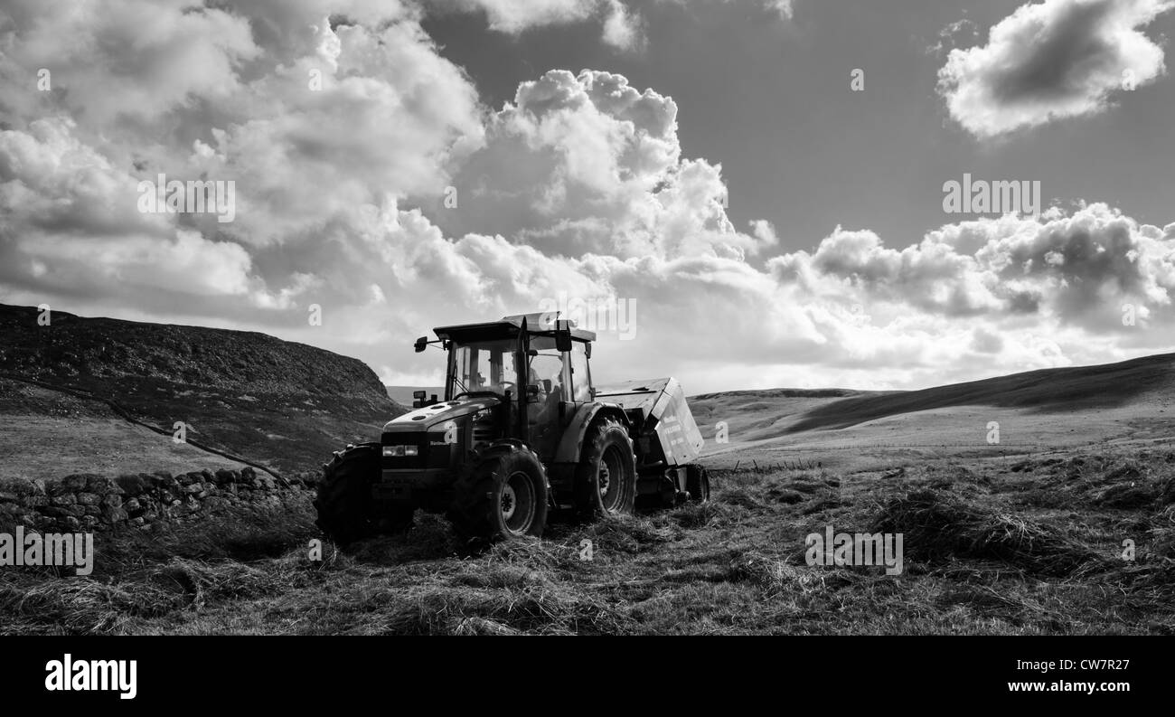 large tractor passes in front of cronkley fell during hay making upper teesdale - Stock Image