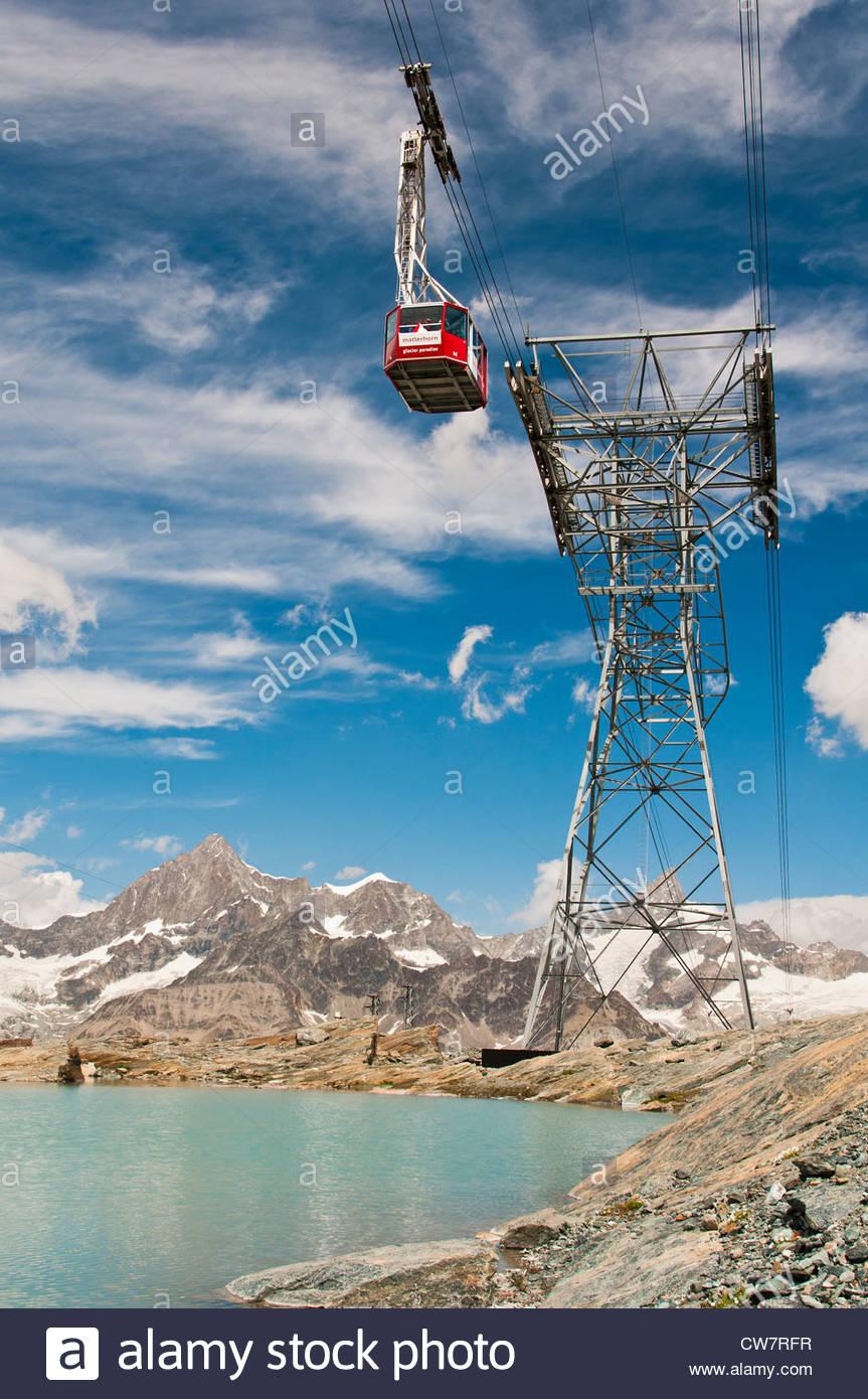 Matterhorn Glacier Paradise aerial tramway or cable car passing above a small mountain lake, Zermatt, Wallis, Switzerland - Stock Image