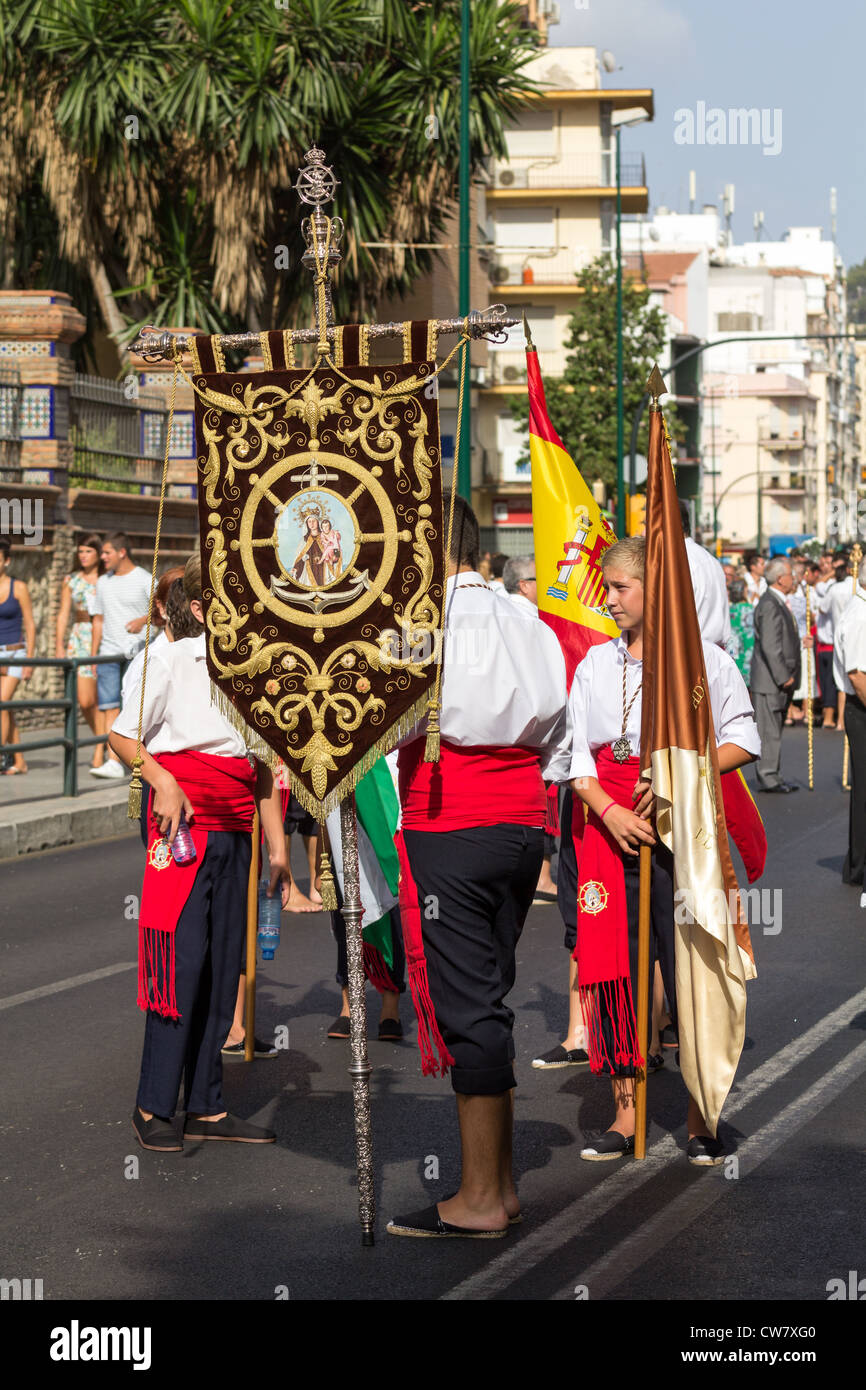 Worshiper with a religious banner in a procession - Stock Image