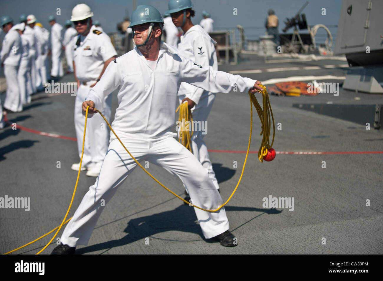 Boatswain's Mate 3rd Class Ron Welch throws heaving line to the forward tug as the guided-missile destroyer - Stock Image