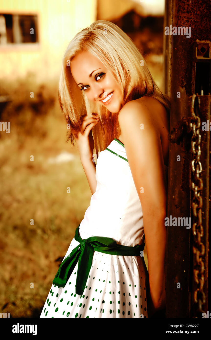 Pretty blond girl happily smiling in green and white dress standing in golden light amongst the abandoned cars at - Stock Image