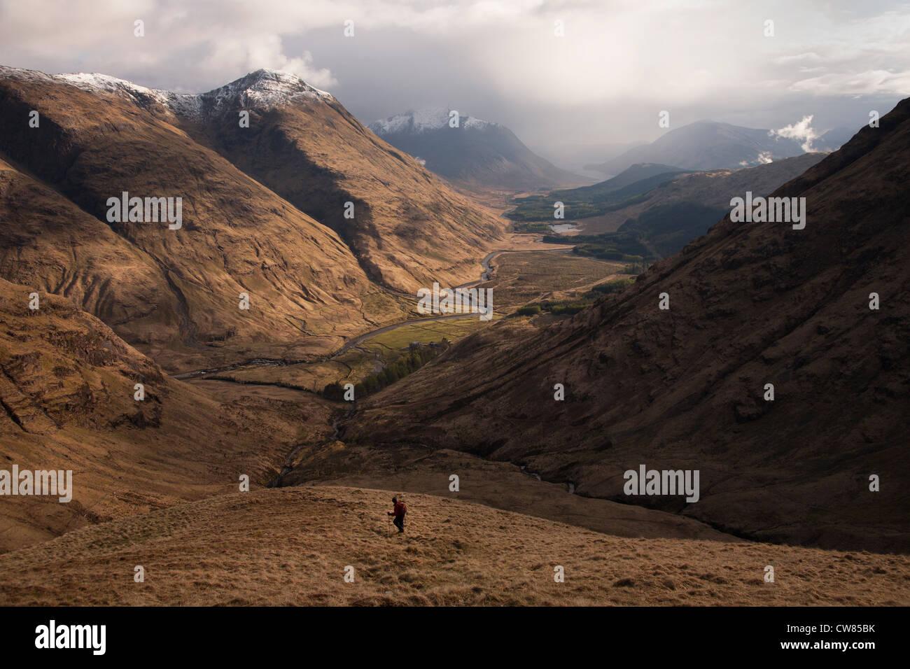 Walker descending into Glen Etive from Buachaille Etive Beag - Stock Image