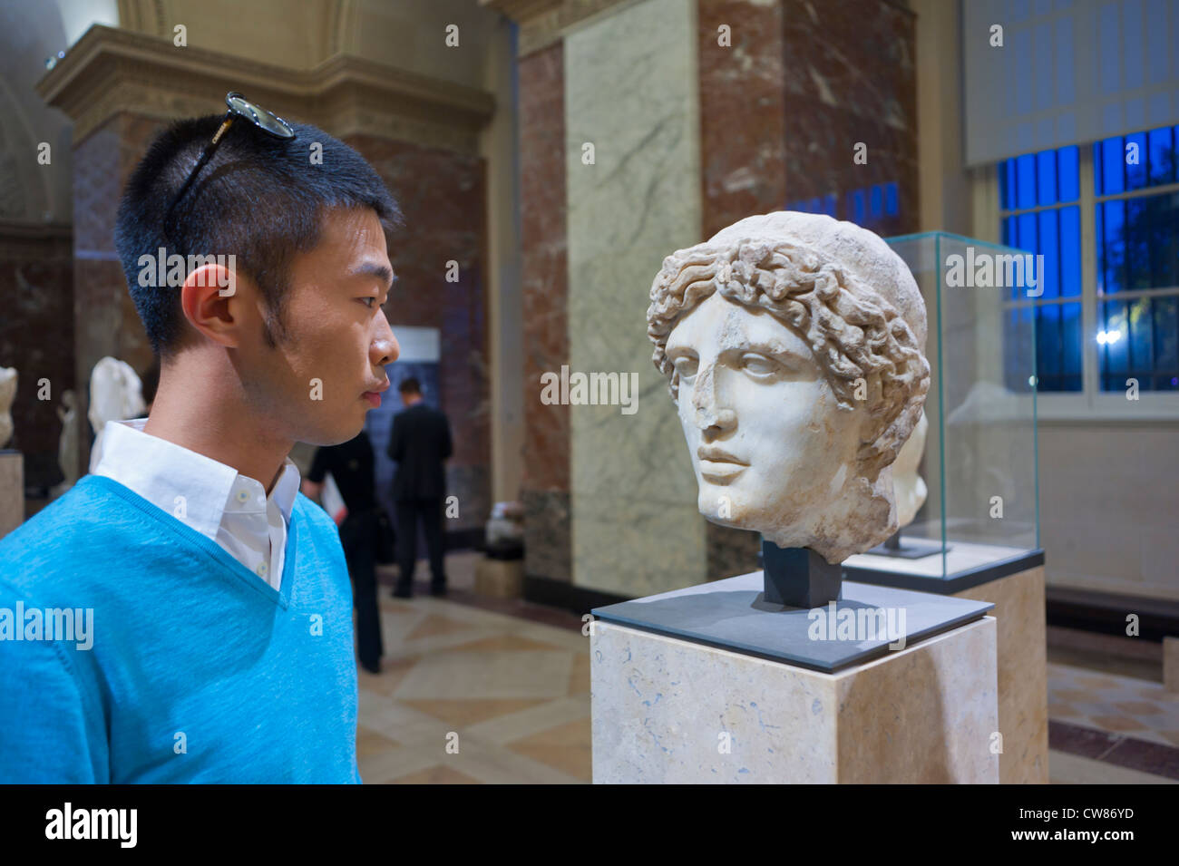 Paris, France, Young Chinese Man Visiting in Louvre Museum, Looking at Greek Antique Statue - Stock Image