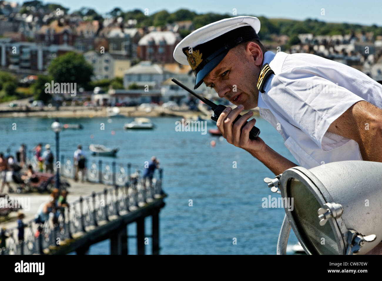 The Captain of the M.V. Balmoral uses a two way radio whilst carrying out docking maneuvers at Swanage Pier - Stock Image
