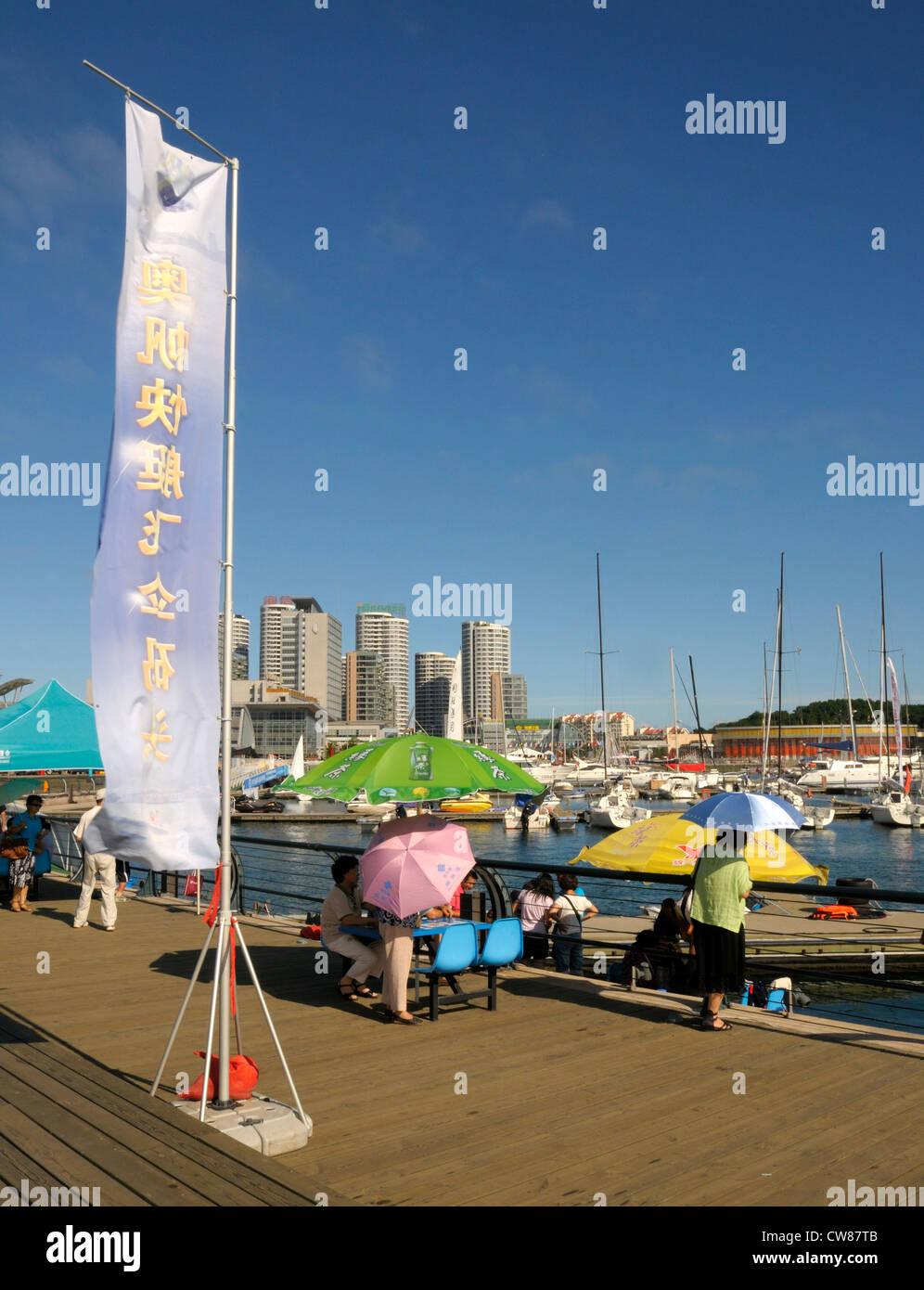 People picnicking in Qingdao marina. - Stock Image