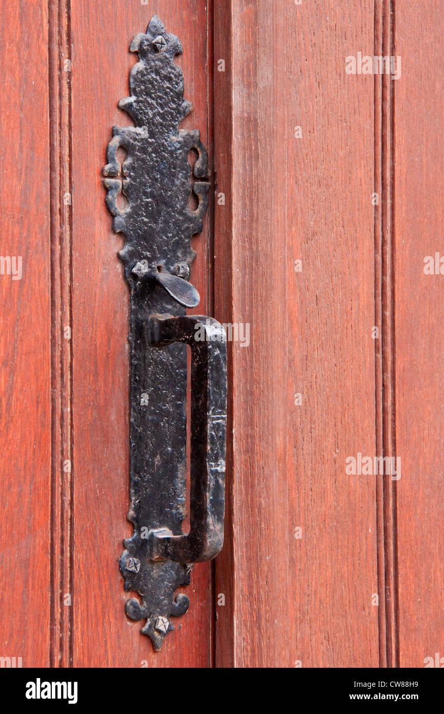 Wrought iron door handle fixed on a massive wood door Stock Photo