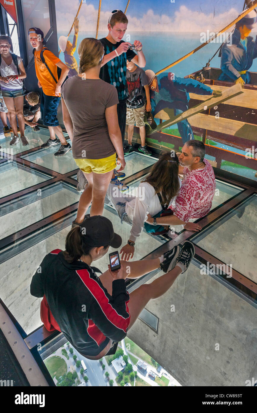 Tourists taking photographs on the Glass Floor at the top of the CN Tower, Toronto, Ontario, Canada - Stock Image