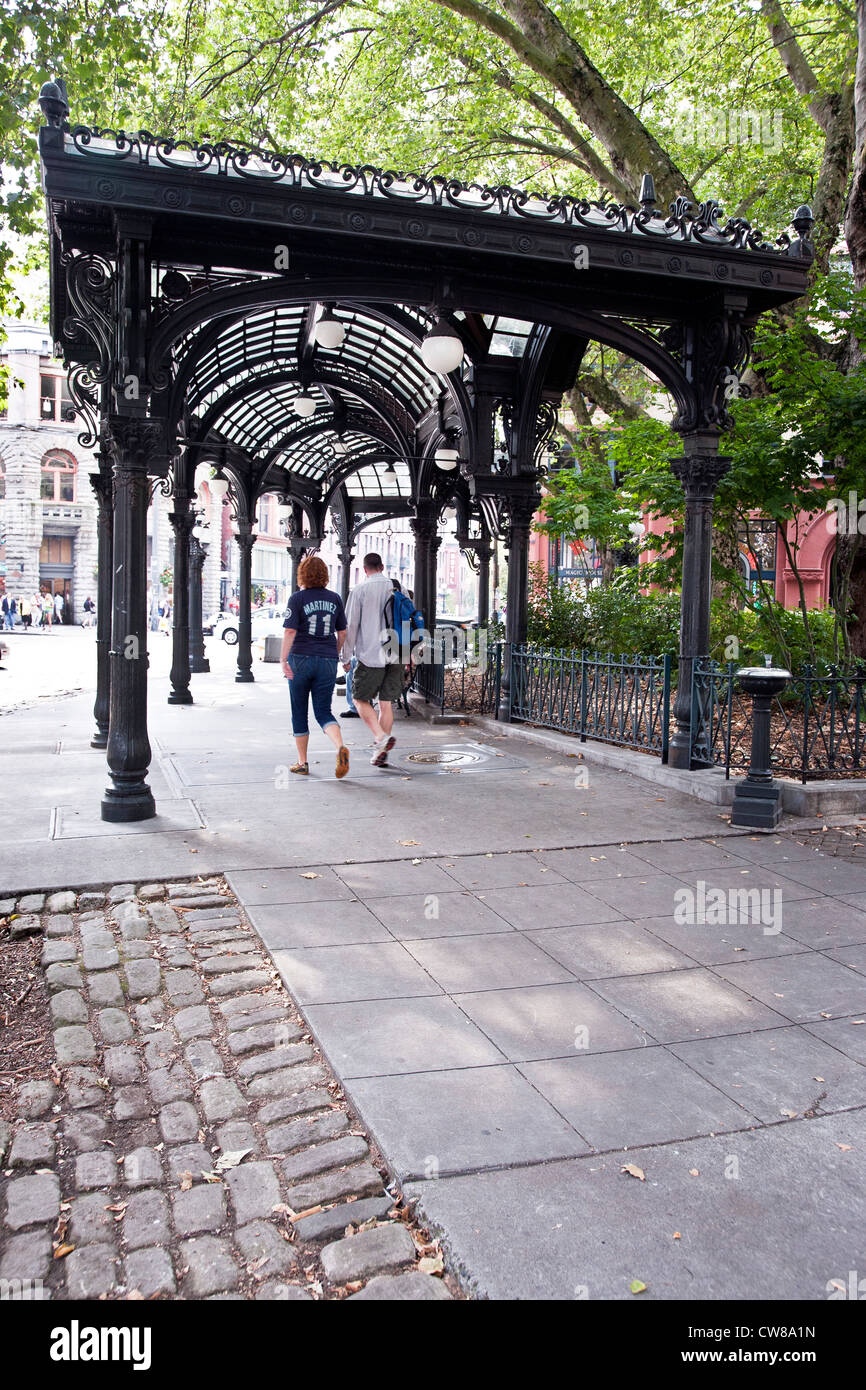 couple walking under arched glass roof & trees overarching elegant  Victorian style cast iron pergola in Pioneer Square Seattle - Couple Walking Under Arched Glass Roof & Trees Overarching Elegant