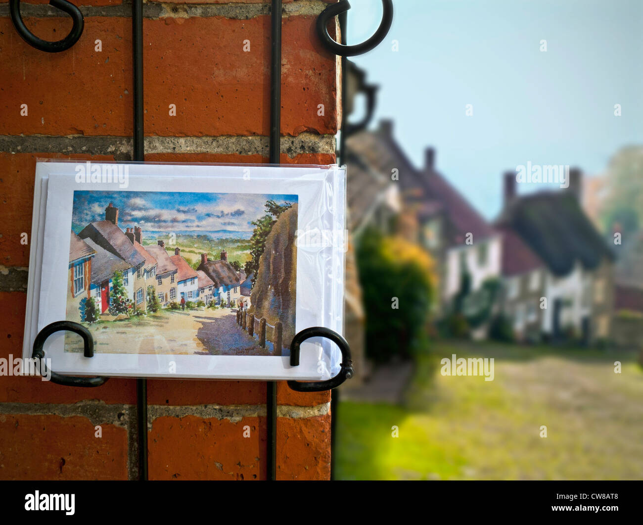 Gold Hill Shaftesbury with local tourist shop postcards in foreground and the featured view behind Dorset UK - Stock Image