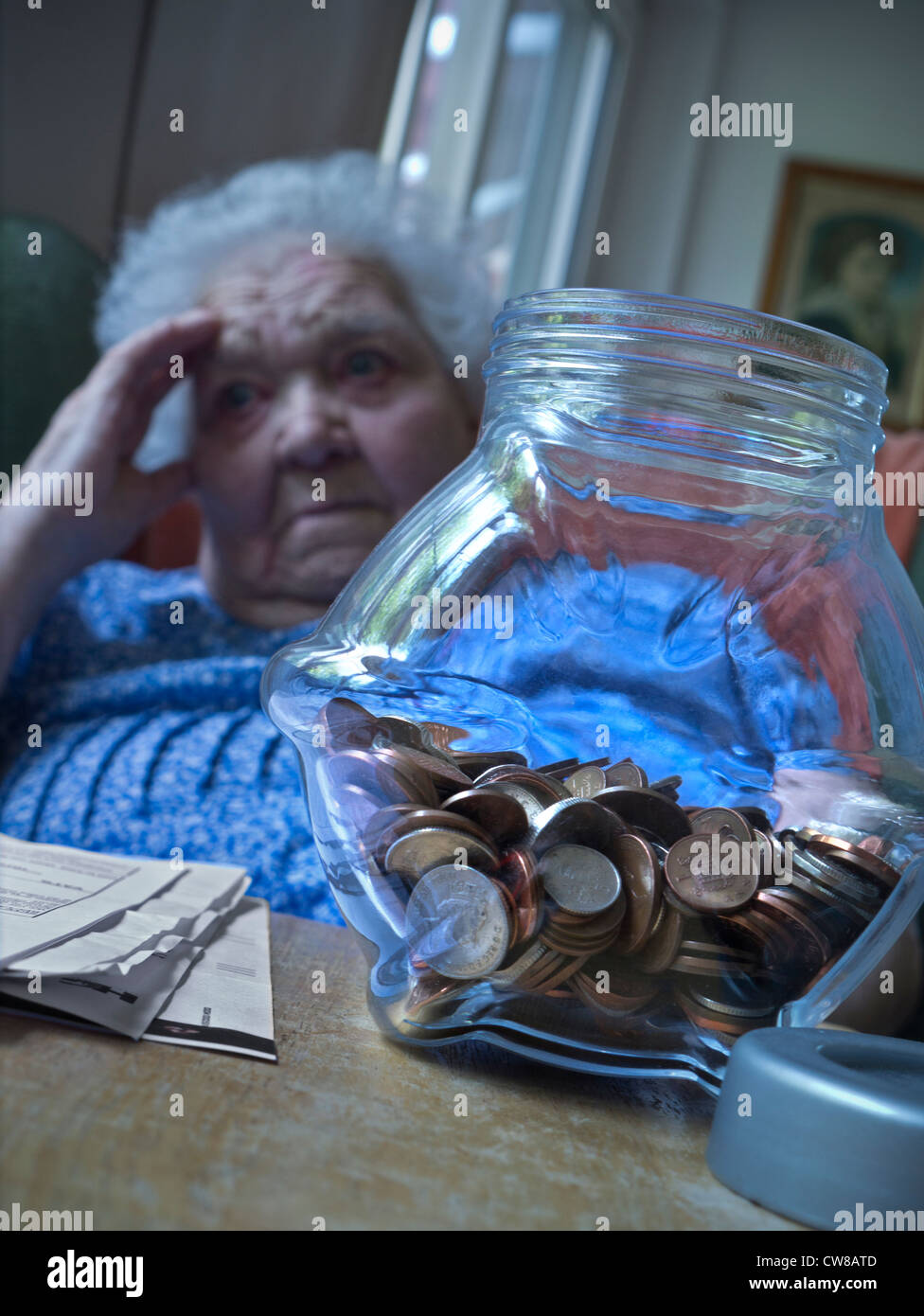 Apprehensive worried vulnerable senior elderly old age lady in her living room with savings pot and papers on table - Stock Image