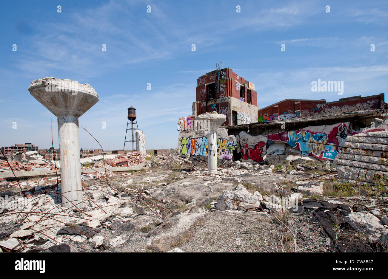 Roof top of an abandoned car manufacturing plant in Detroit Michigan. The ceiling supports have toppled over graffiti - Stock Image