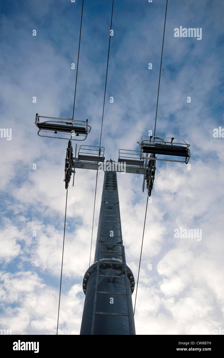 Empty chairlifts against cloudy blue sky Stock Photo