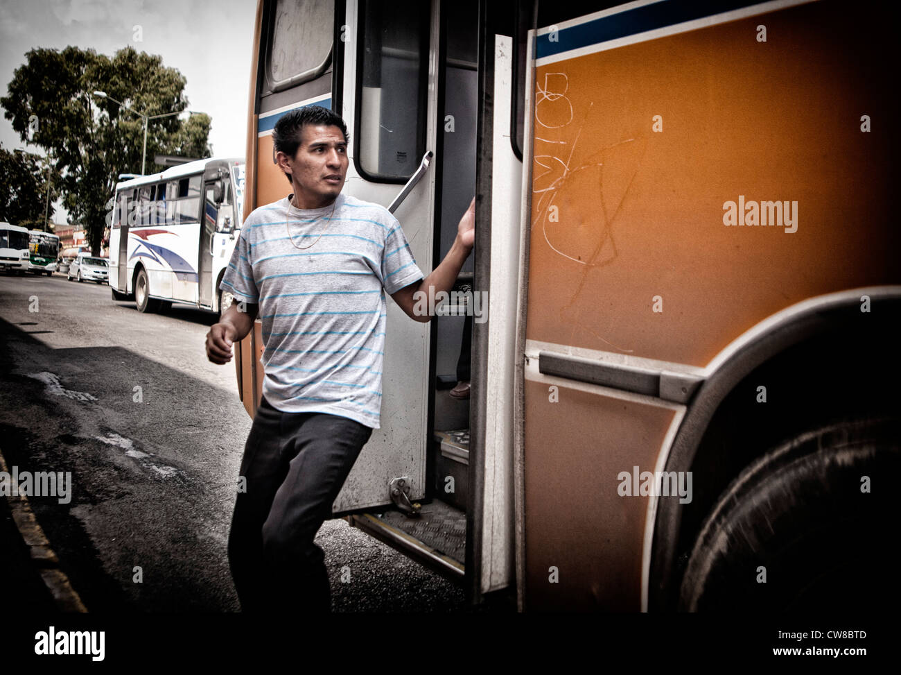 Man getting off of a bus in Puebla, Mexico - Stock Image