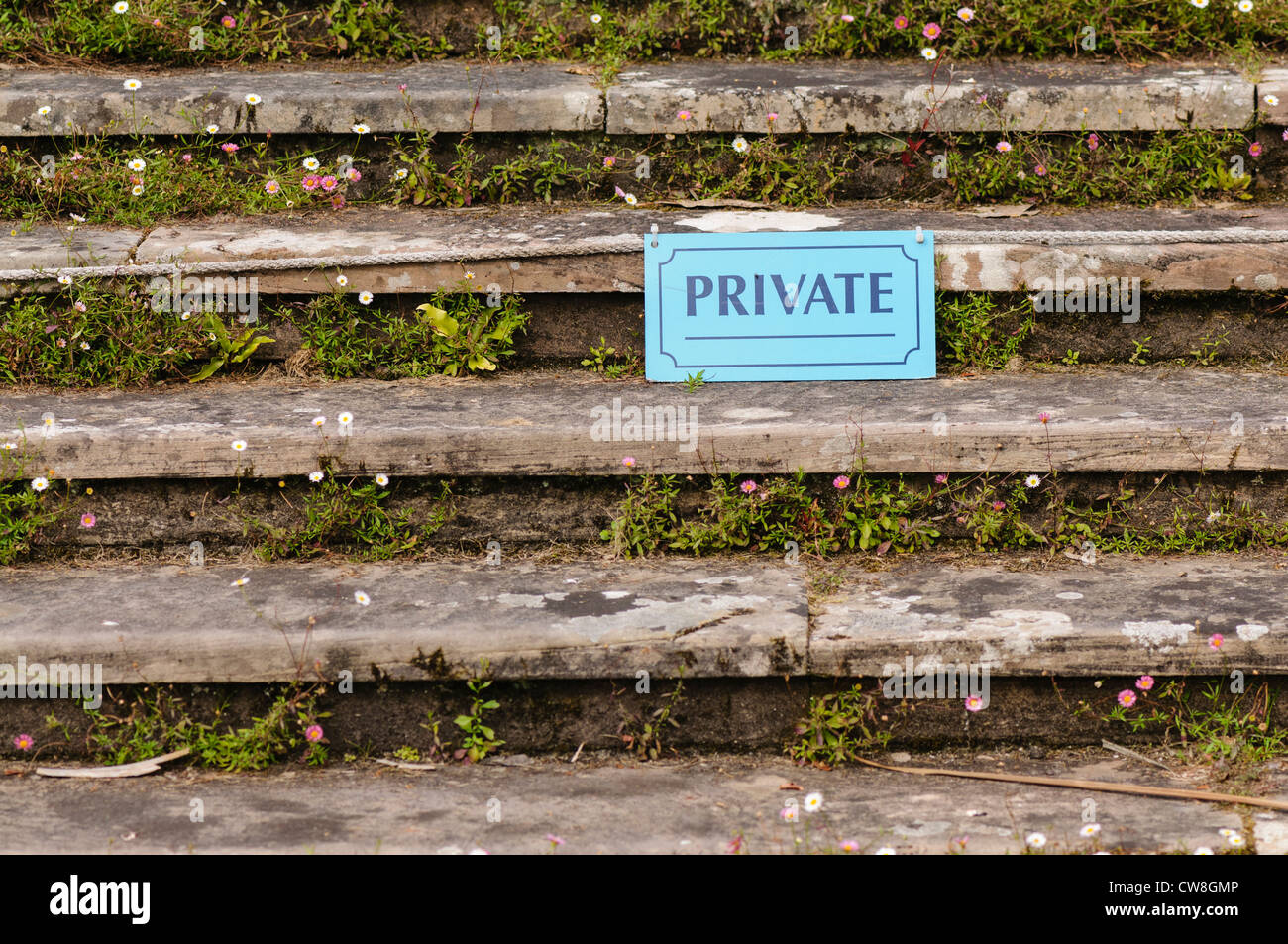Sign saying 'private' on stone steps covered in flowers - Stock Image