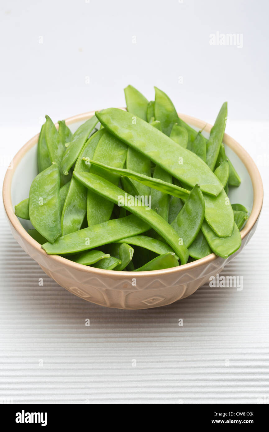 Mange Tout, Sugar snap Peas in bowl on plain Background - Stock Image
