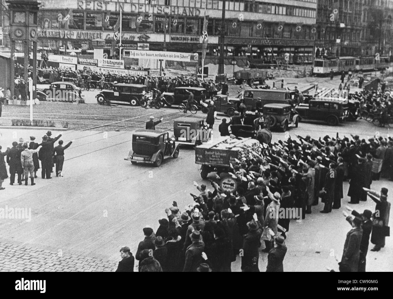 In Berlin passers-by saluting Führer. They hear his voice on radio (1933) - Stock Image