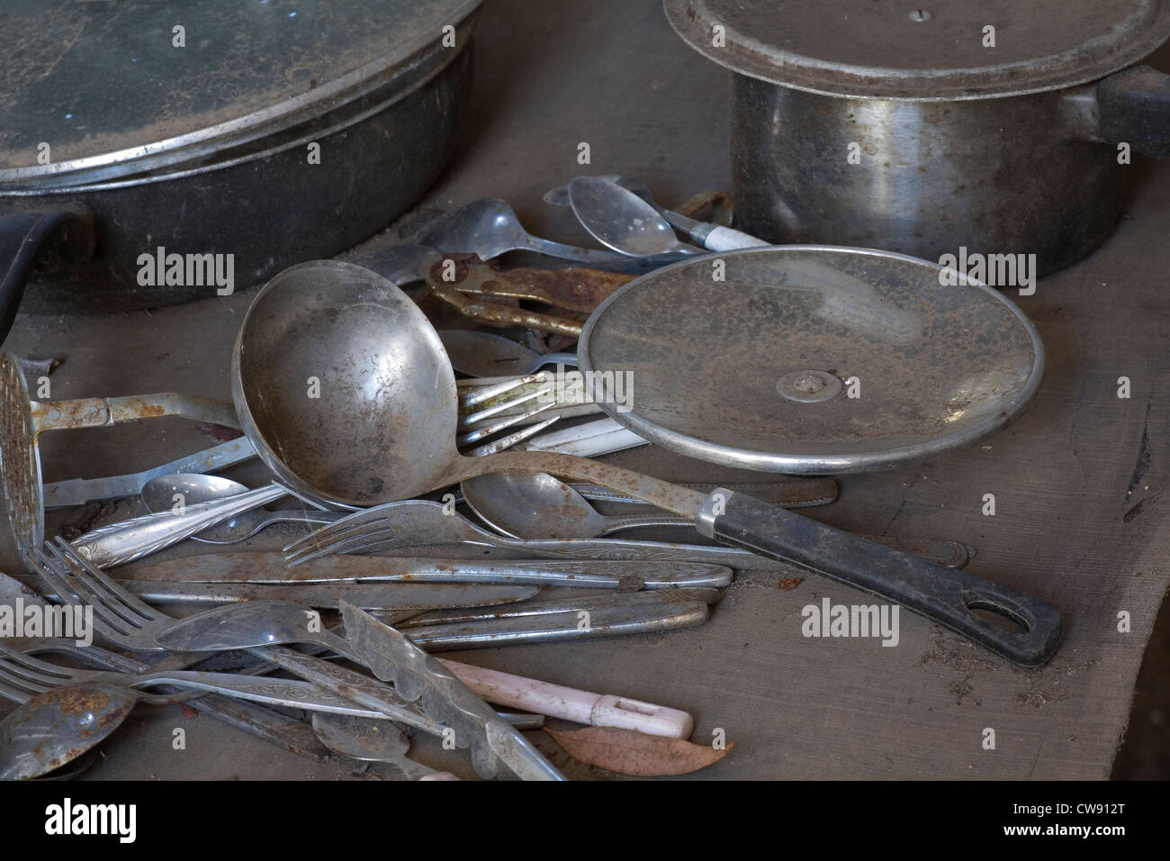 Rusty and dirty old kitchen utensils in a long abandoned shack. - Stock Image