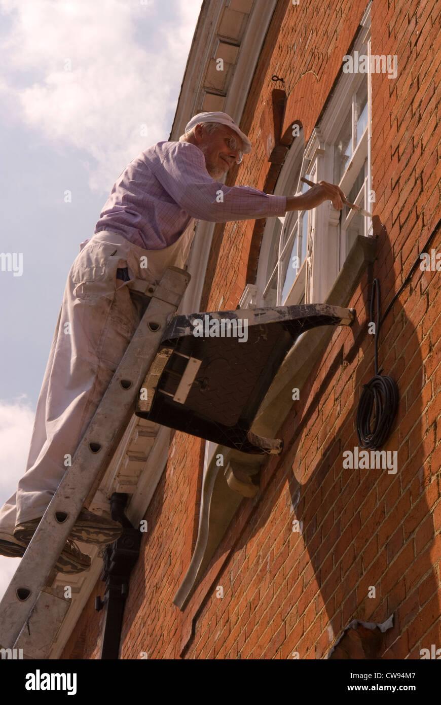 Painter and decorator aloft ladder painting facade of building, Farnham, Surrey, UK. - Stock Image