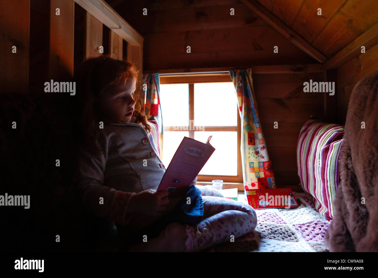 Little girl reading a book in her playhouse den - Stock Image