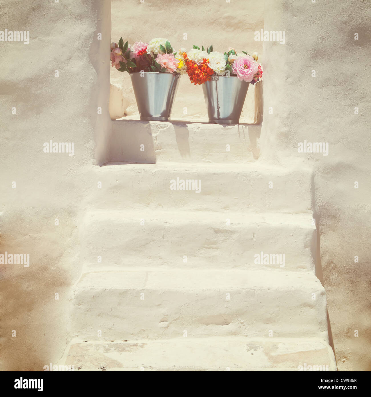 A staircase of a Greek, white house with two bunches of flowers - Stock Image