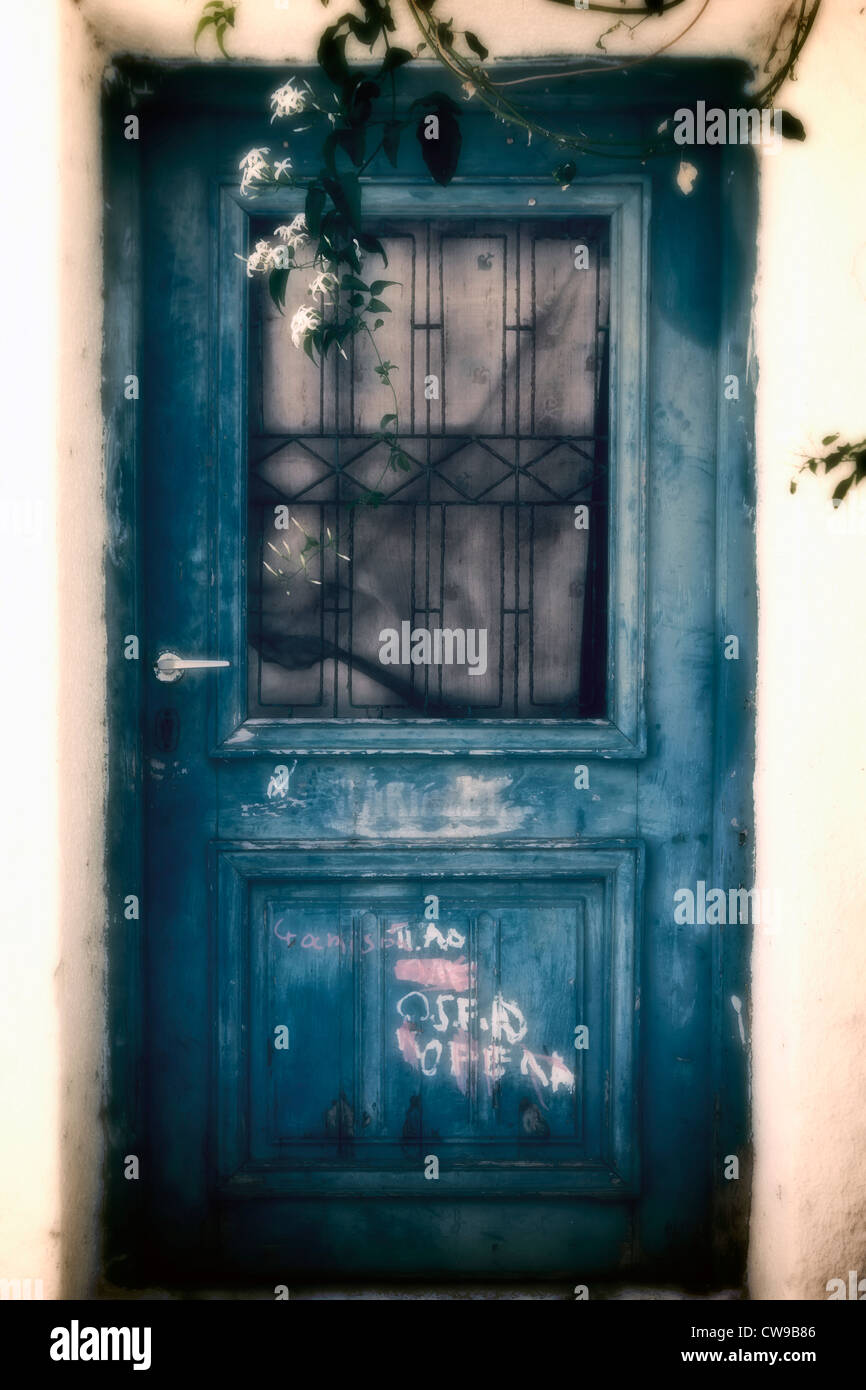 an old blue wooden door with graffiti and lattice - Stock Image