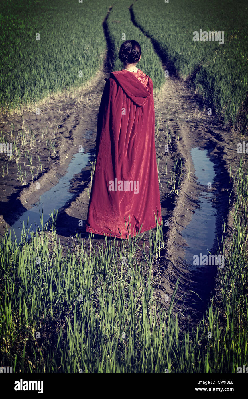 a woman in a red cape standing on a fiel in the mud - Stock Image