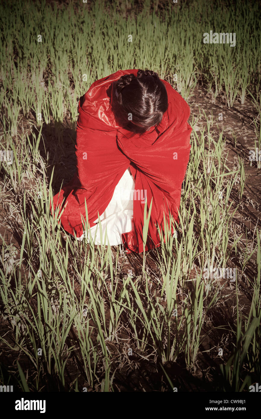 a woman in a red cloak crouching in a field - Stock Image