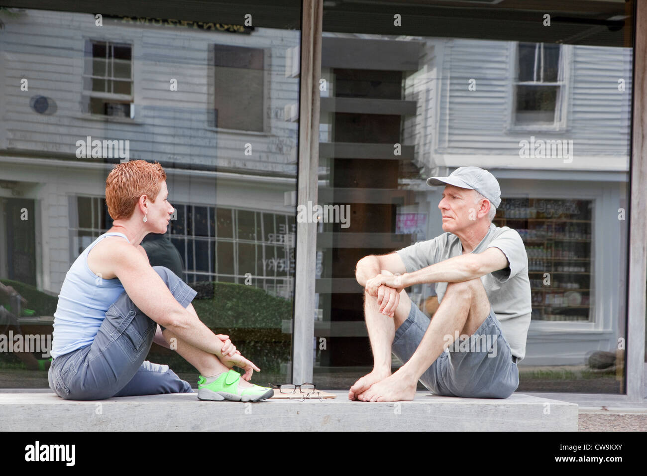 Woman and man talking while sitting on a bench outdoors. - Stock Image