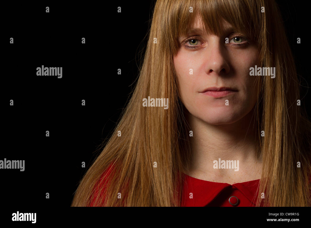 38 year old woman looking to camera, in front of black background. - Stock Image