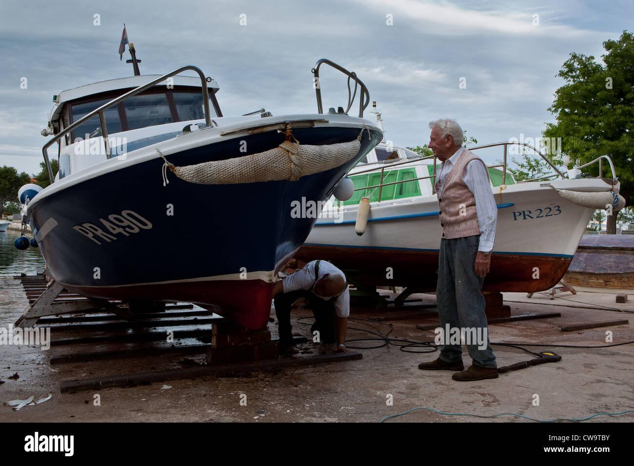 Man repairing boats in small port Poljana, island Ugljan, Dalmatia, Croatia - Stock Image