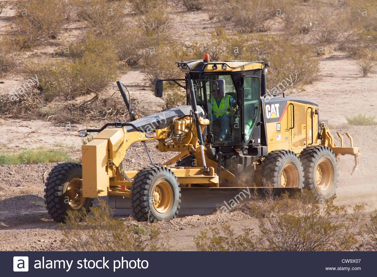 Caterpillar 140M Grader grading road operator visible in cab Arizona - Stock Image