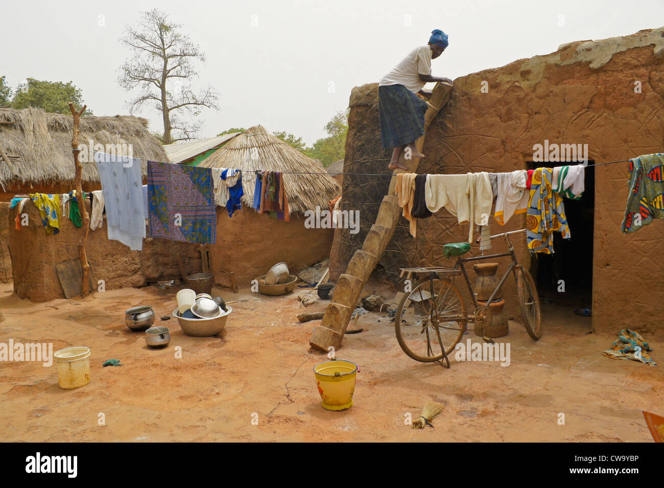 Woman on log ladder in family compound, Mognori Eco-Village, Ghana - Stock Image