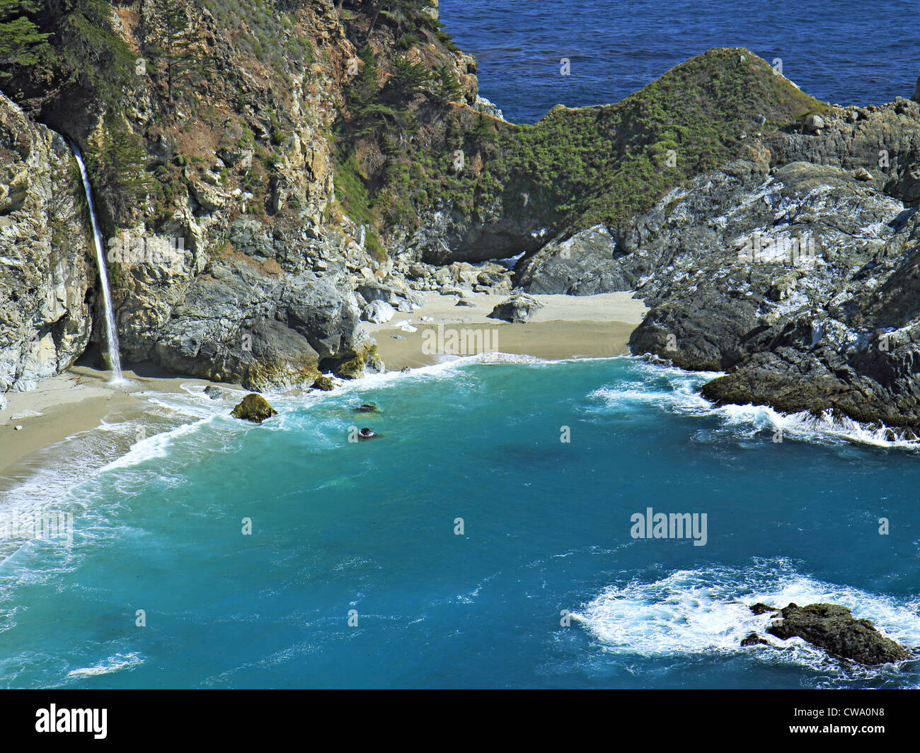 Beautiful waterfall pouring onto beach in blue ocean cove. - Stock Image