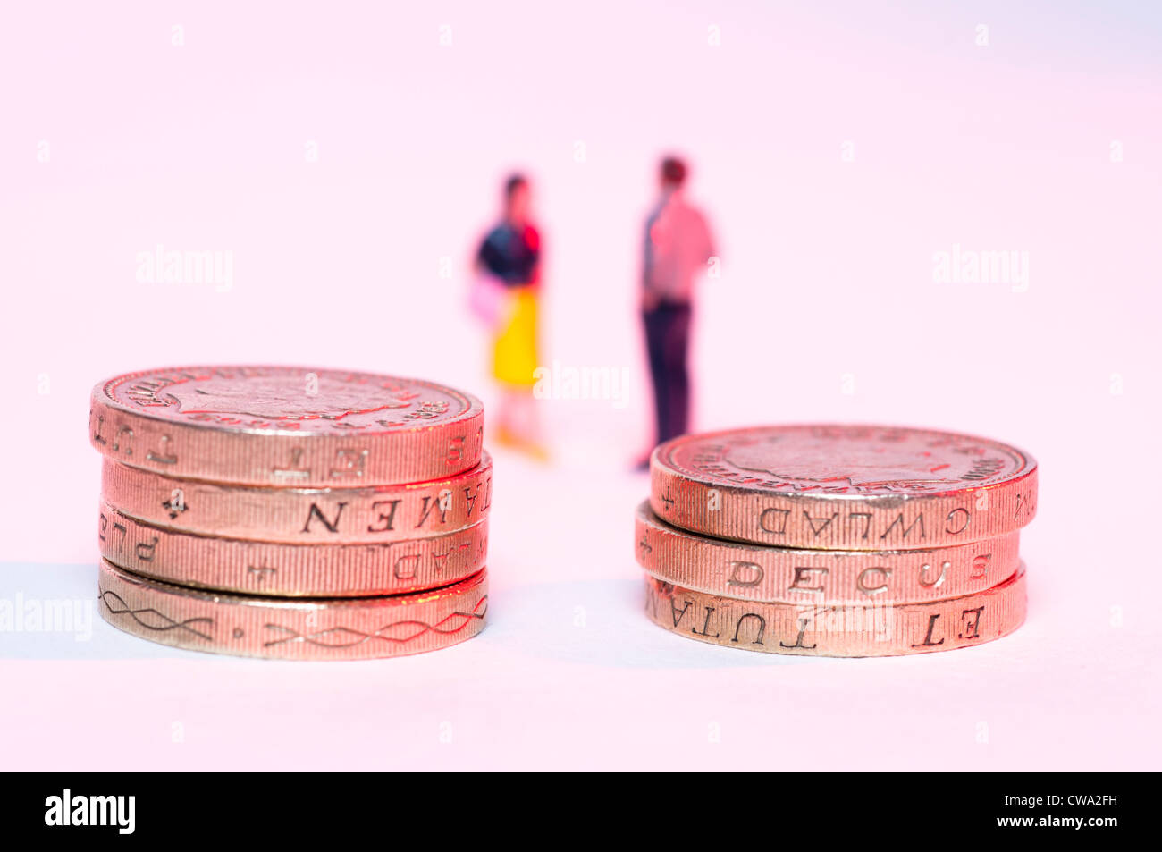 Stacked up one pound coins and blurred couple in background Stock Photo