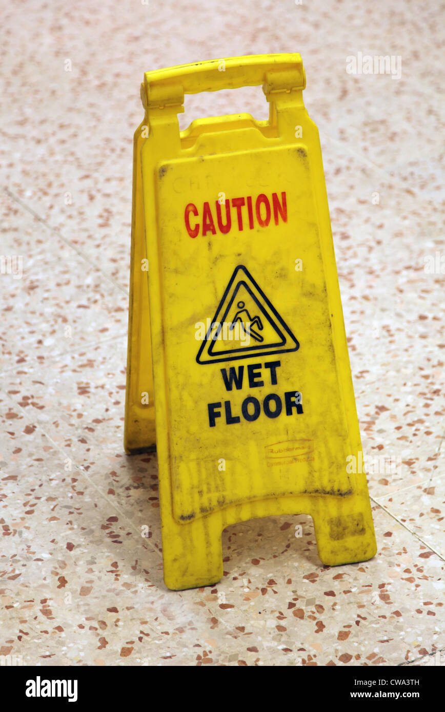 It's a photo of a yellow caution sign to indicate a wet floor or slippery floor in a mall or supermarket. It - Stock Image