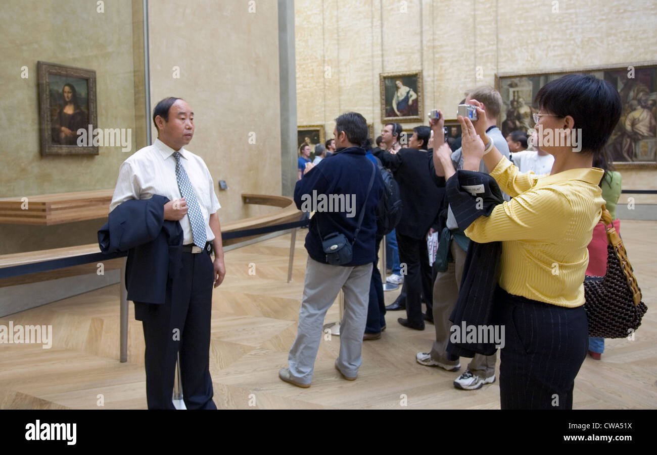 Paris, a man is photographed in front of the painting of the Mona Lisa in the Louvre - Stock Image