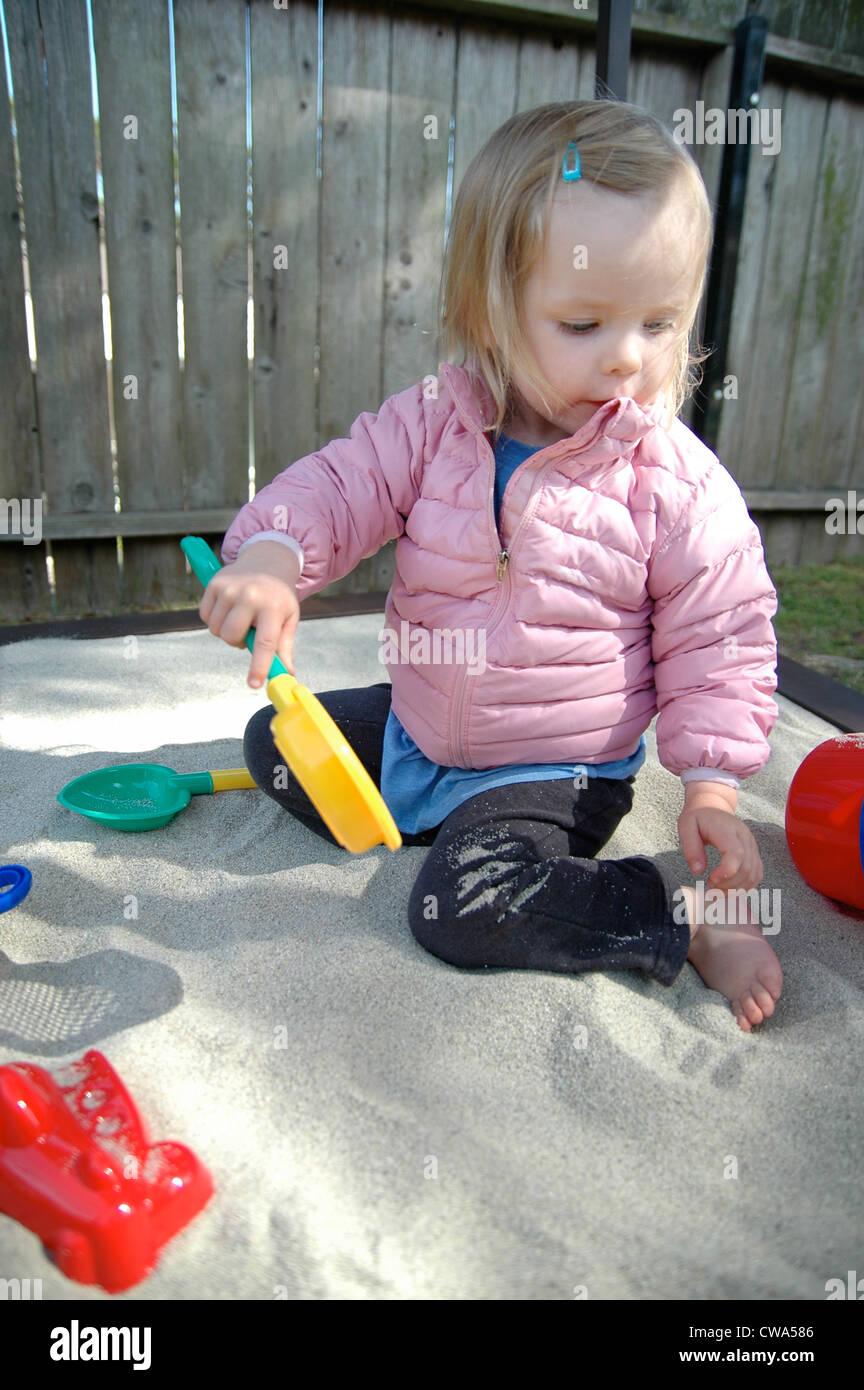 Little Girl Playing In Sandbox Stock Photo