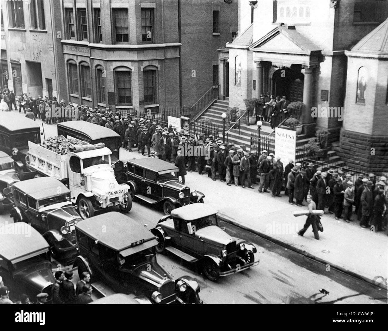 DEPRESSION- Jobless men lined up in front of St. Francis of Assisi Church waiting to receive a nickel each from - Stock Image
