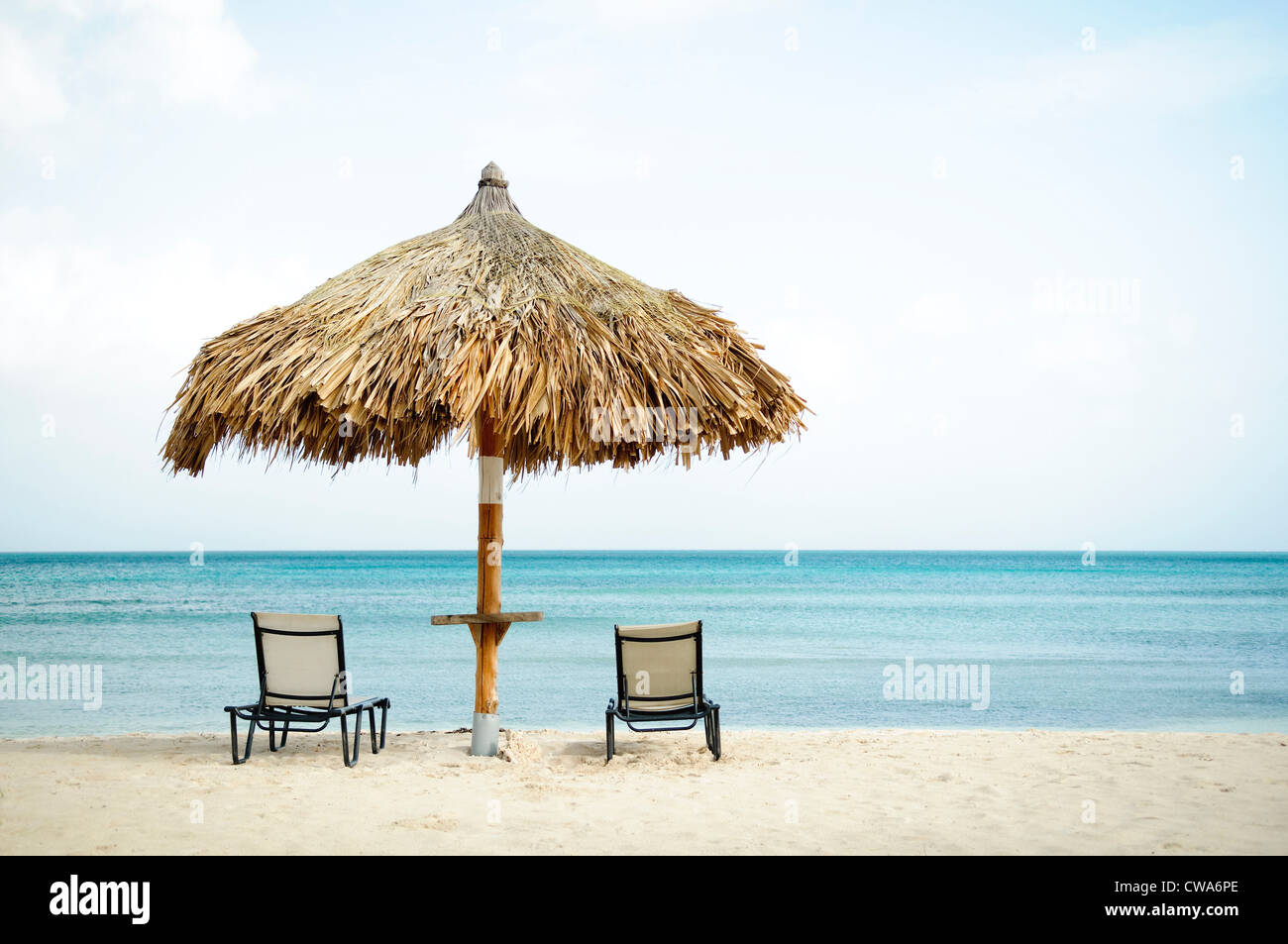 Parasol and sun loungers on beach - Stock Image