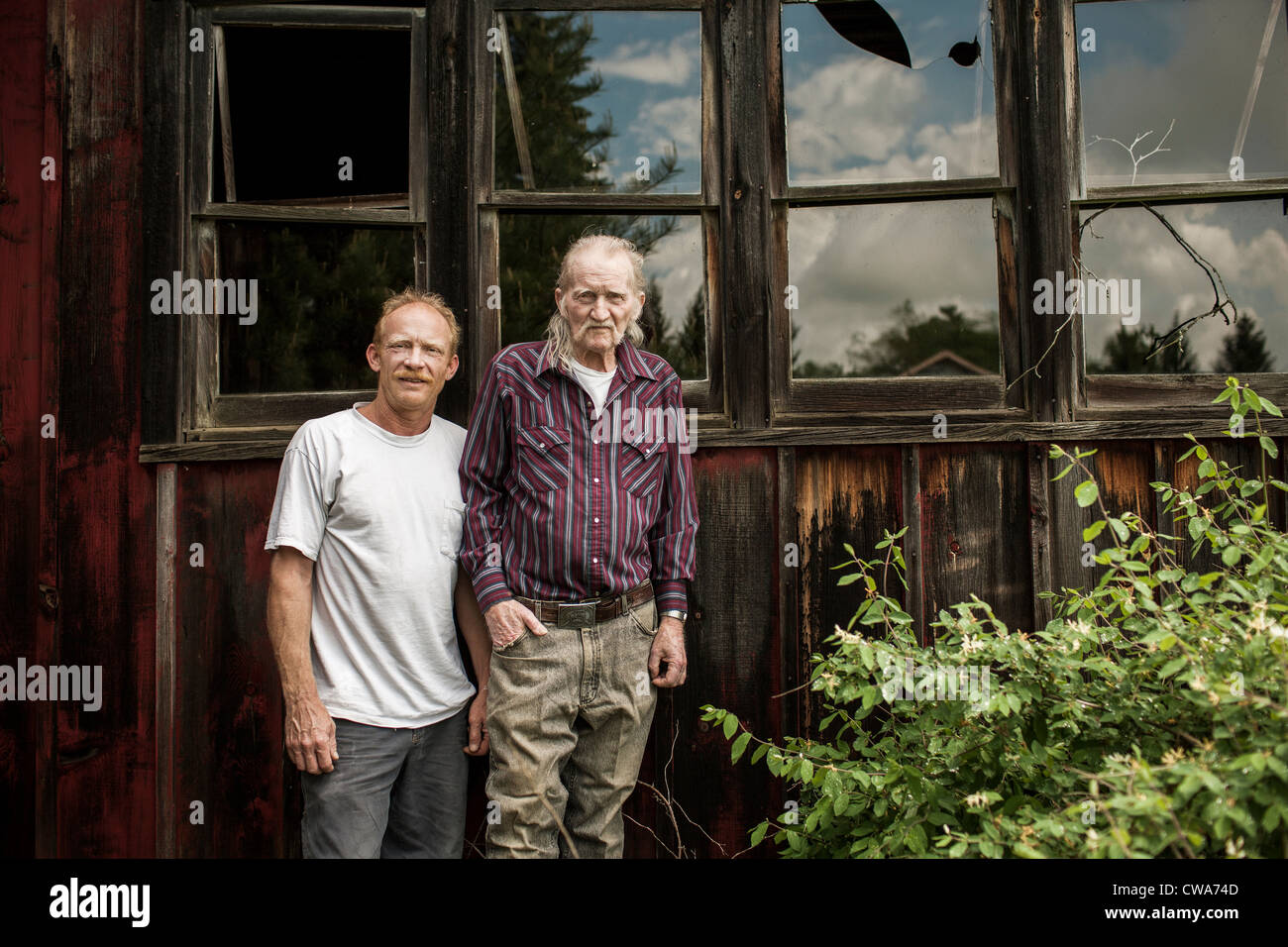 Father and son outside shack, portrait - Stock Image