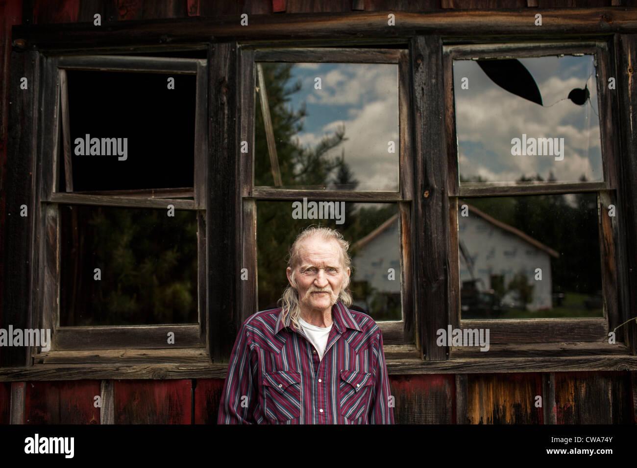 Senior man outside shack, portrait - Stock Image