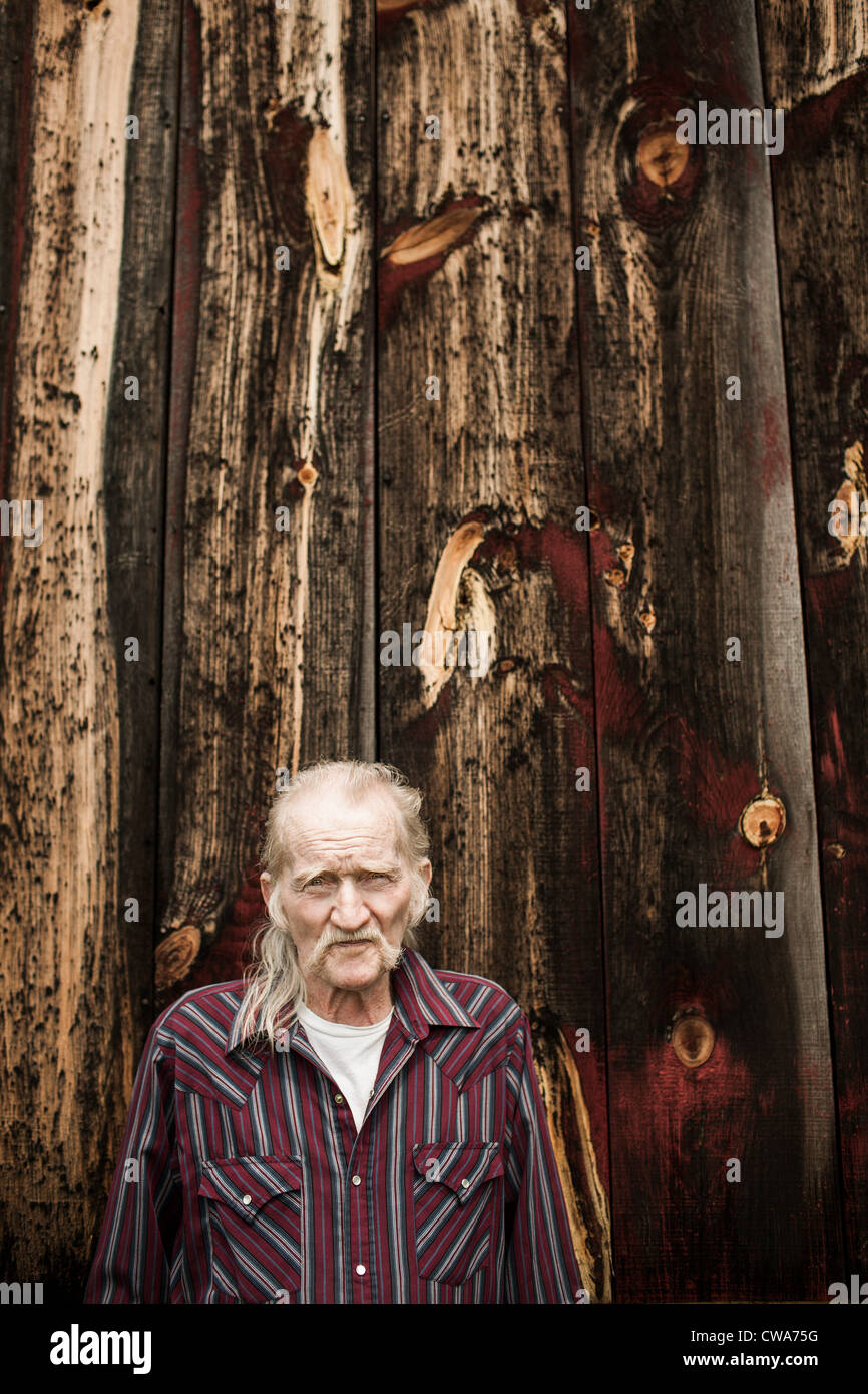 Senior man outside barn, portrait - Stock Image