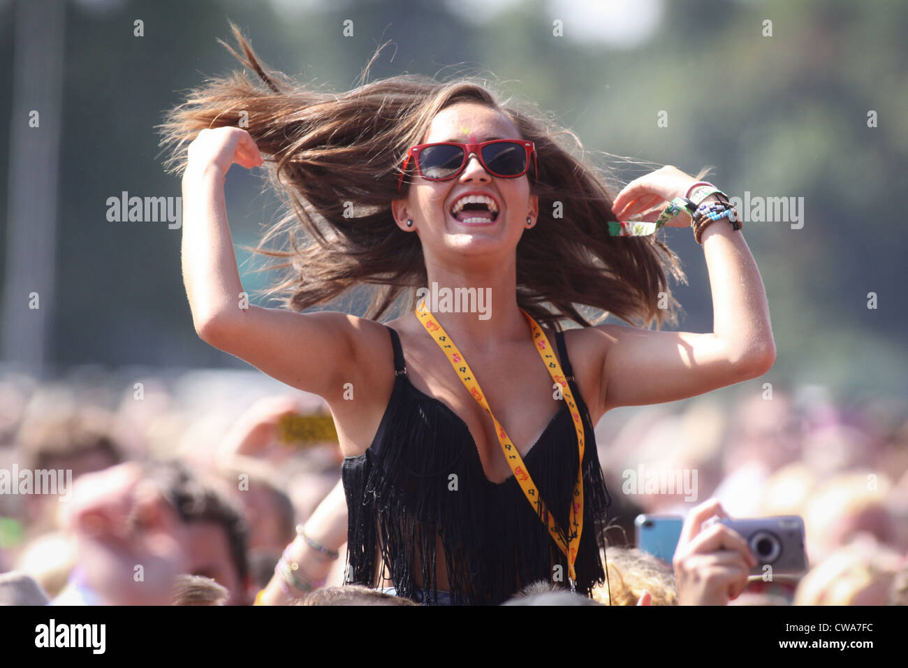 A girl in the crowd enjoying the live music at the V Festival in Hylands Park, Chelmsford, Essex - Stock Image