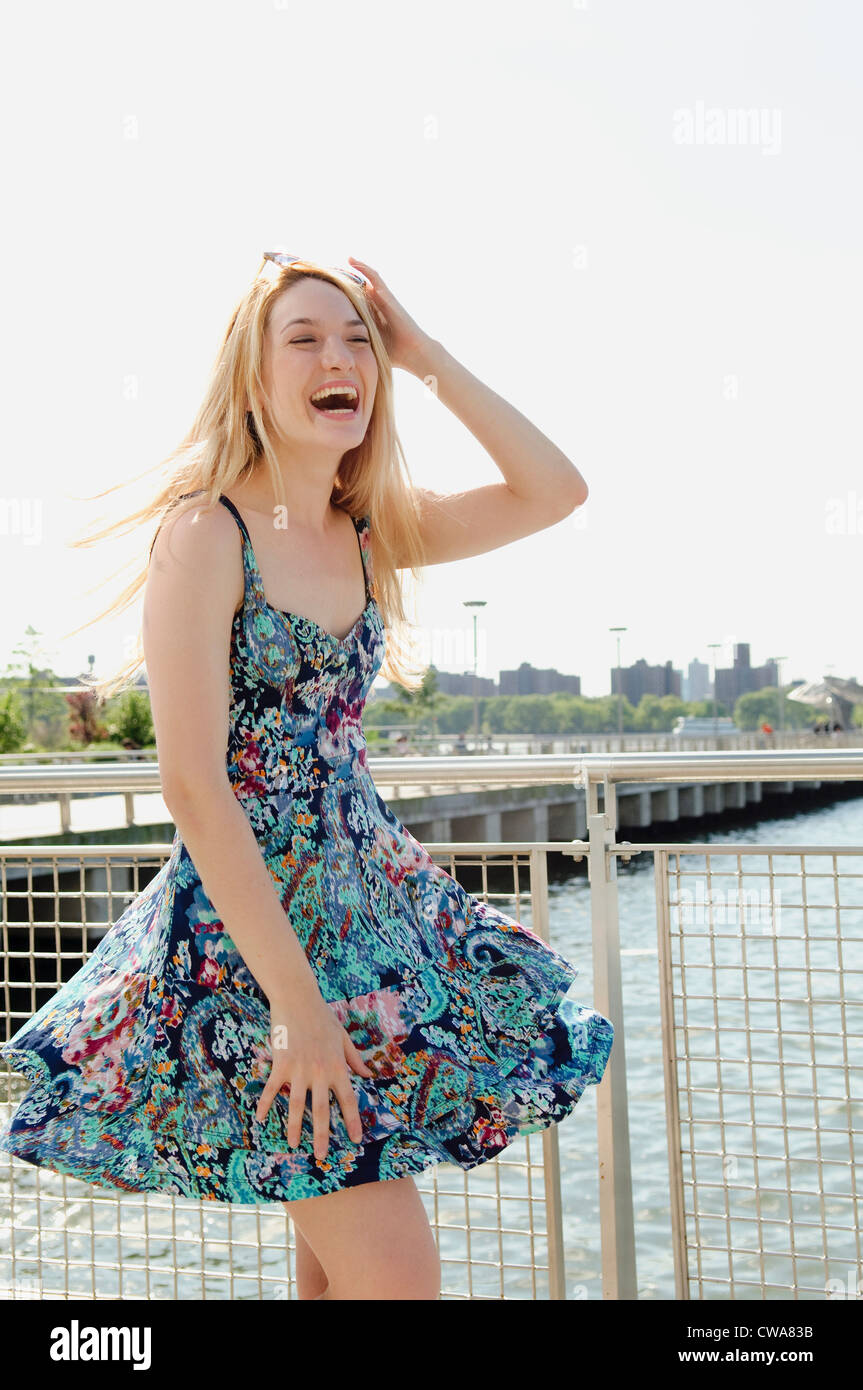 Young woman by waterfront, laughing - Stock Image