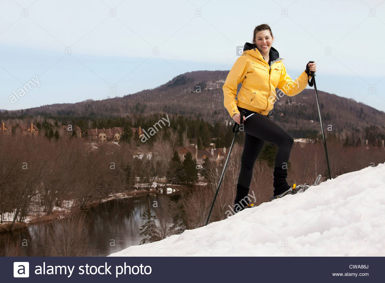 Young woman in skis walking uphill - Stock Image