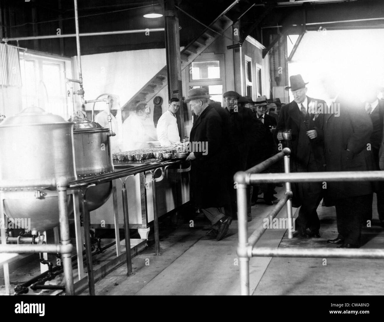 Men wait in line for food at a municipal lodging house. Police Commissioner Edward P. Mulrooney stands with coffee - Stock Image