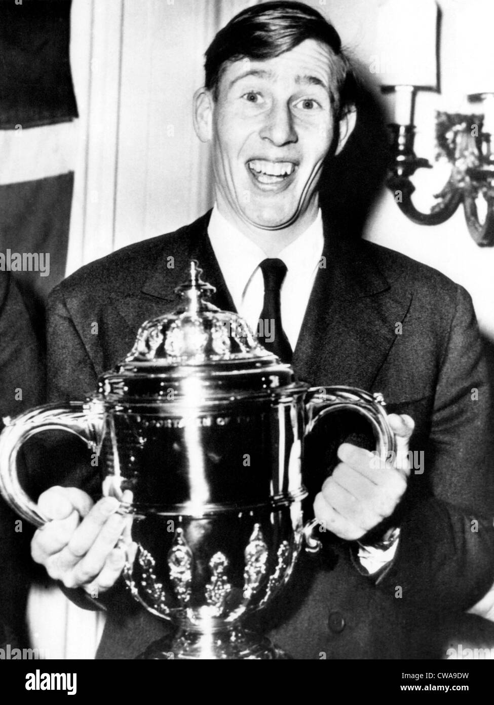 Roger Bannister, the first person to run a mile in less than four minutes, holds a Sporting Record Trophy, 1954. - Stock Image