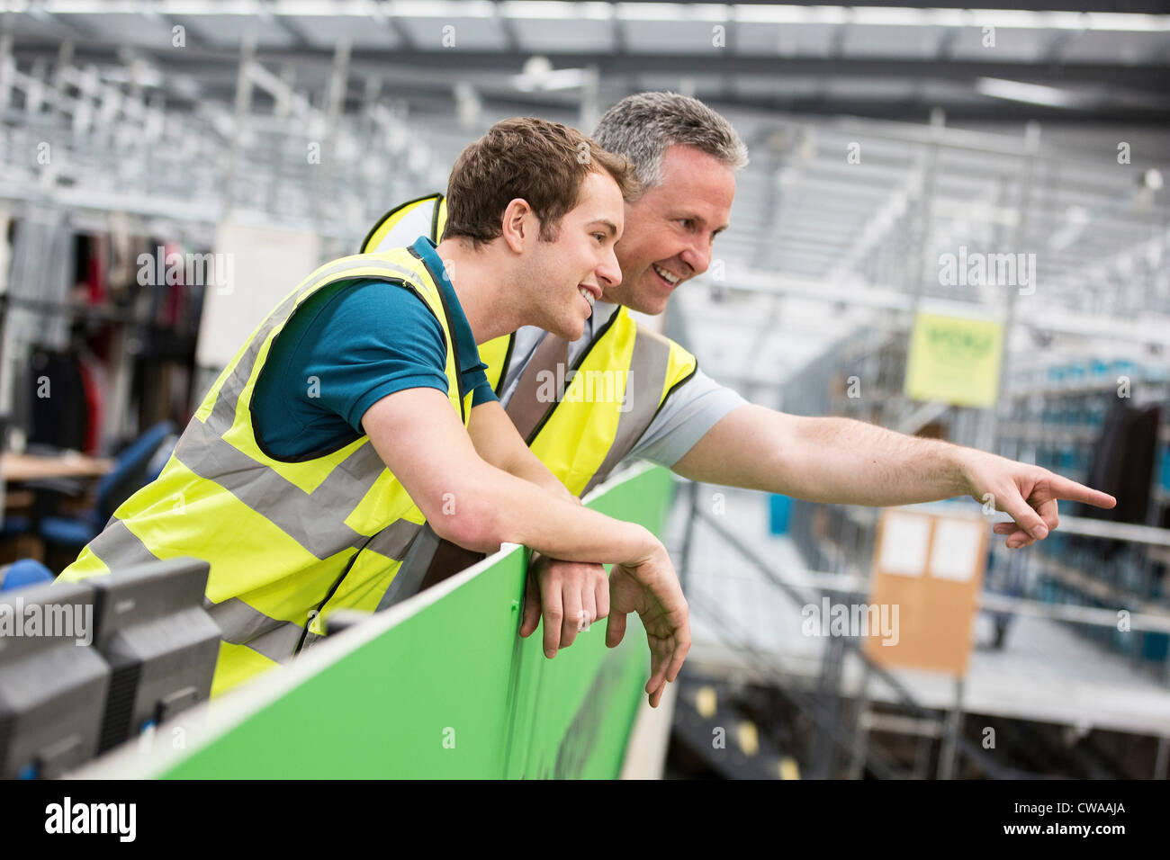 Two men in warehouse, one pointing - Stock Image