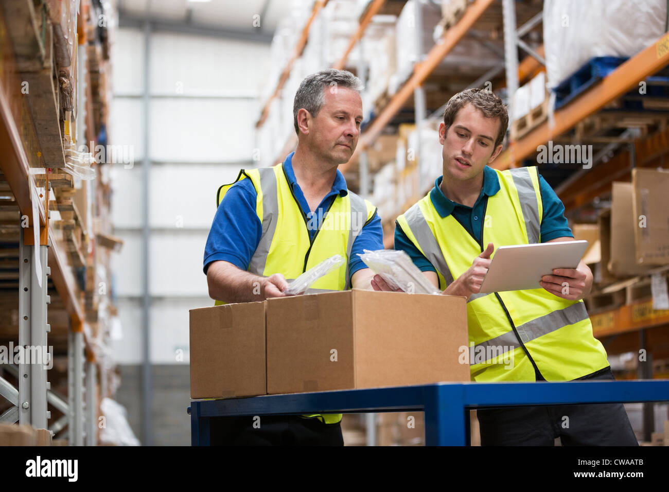 Two men checking stock in warehouse - Stock Image