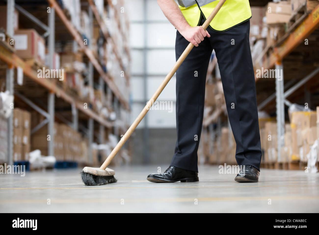 Man sweeping warehouse floor with broom - Stock Image